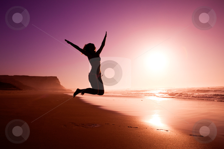 Jumping on the beach stock photo, Picture of a female silhouette of a young girl jumping on the beach at the sunset by ikostudio