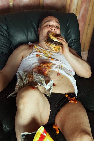 Couch potato eating and watching TV stock photo, Photo of a fat couch potato eating a huge hamburger and watching television.  Harsh lighting from the television illuminates the dark room.  by © Ron Sumners