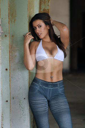 Beautiful Latina at an Abandoned Warehouse (18) stock photo, Medium shot of a lovely young Latina, wearing jeans-style leggins and a bikini top, at an old, abandoned warehouse. by Carl Stewart
