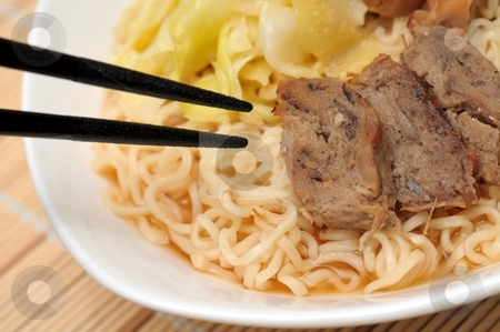 Chopsticks eating delicious noodles stock photo, Japanese style chopsticks eating tasty yellow noodles with meat pieces. by Wai Chung Tang