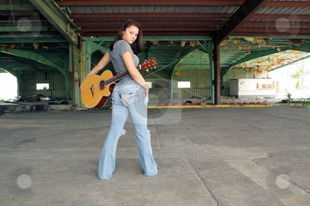 Beautiful Brunette with a Guitar (2) stock photo, A lovely young brunette wearing tattered jeans, stands with her back to the camera, looking over her shoulder,holding a guitar at an abandoned warehouse facility. by Carl Stewart