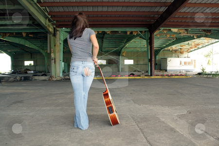 Beautiful Brunette with a Guitar (3) stock photo, A lovely young brunette wearing tattered jeans, stands with her back to the camera with a guitar at her side, at an abandoned warehouse facility. by Carl Stewart