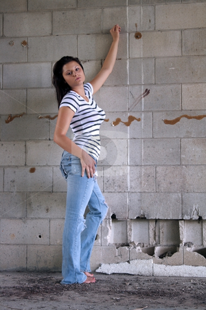 Sexy Brunette at a Block Wall (3) stock photo, A lovely young brunette wearing tattered jeans and a white T-shirt with black stripes, leans against an old, dilapidated block wall. by Carl Stewart