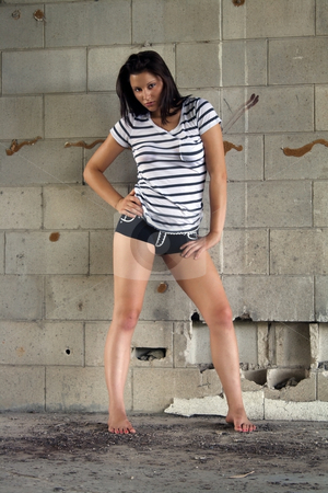 Sexy Brunette at a Block Wall (8) stock photo, A lovely young brunette wearing black boy shorts with white patterns and a white T-shirt with black stripes, stands facing the camera in front of an old, dilapidated block wall. by Carl Stewart