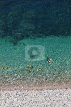 Diving in turquoise water stock photo, Nude woman swimming in turquoise water by Bernardo Varela