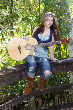 Beautiful Teen Girl with Guitar (3) stock photo, A lovely teenage girl sits on a wooden fence rail with her acoustic guitar. by Carl Stewart