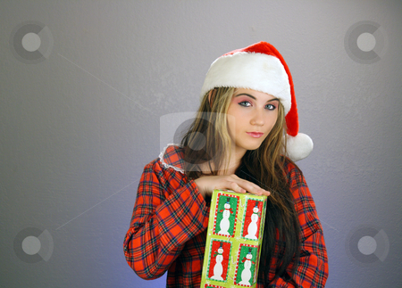 Teen Girl Santa's Helper (2) stock photo, A beautiful teenage girl wearing a Santa's helper hat and a comfy flannel nightgown, holds a wrapped gift.  Plenty of room on frame left for inserting text, graphics, etc.  Textured background. by Carl Stewart