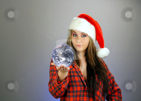 Teen Girl Santa's Helper (4) stock photo, A beautiful teenage girl wearing a Santa's helper hat and a comfy flannel nightgown, holds the earth in the palm of her hand.  Plenty of room on frame left for inserting text, graphics, etc.  Textured background.  Earth photo credit:  NASA (public domain) by Carl Stewart