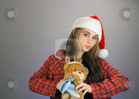 Teen Girl Santa's Helper (6) stock photo, A beautiful teenage girl wearing a Santa's helper hat and a comfy flannel nightgown, holds a sleepy teddy bear.  Plenty of room on frame left for inserting text, graphics, etc.  Textured background. by Carl Stewart