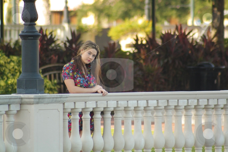 Beautiful Teen Girl Outdoors (7) stock photo, A lovely teenage girl wearing a floral print dress standing behind a patterned railing with lush, tropical vegetation in the background. by Carl Stewart