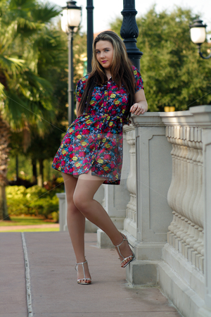 Beautiful Teen Girl Outdoors (8) stock photo, A lovely teenage girl wearing a floral print dress standing beside a patterned railing with lush, tropical vegetation in the background. by Carl Stewart