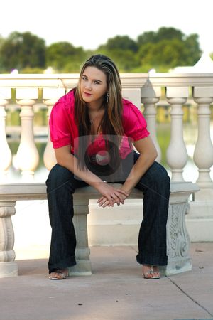 Beautiful Teen Girl Sitting on an Outdoor Bench (2) stock photo, A lovely teenage girl sits fashionably on an outdoor bench. by Carl Stewart