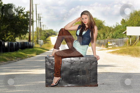 Teen Girl on a Trunk in the Street (2) stock photo, A lovely teenage girl sits fashionably on an antique trunk in the middle of a lonely country road. by Carl Stewart
