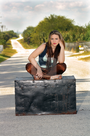 Teen Girl on a Trunk in the Street (3) stock photo, A lovely teenage girl sits fashionably on an antique trunk in the middle of a lonely country road. by Carl Stewart