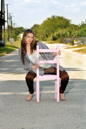 Teen Girl Sitting in a Chair in a Roadway (1) stock photo, A lovely teenage girl sits fashionably in a pink wooden chair in the middle of a lonely country road. by Carl Stewart
