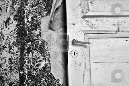 Torn wallpaper stock photo, Torn wallpaper and old door in abandoned house. Black and white. by sirylok