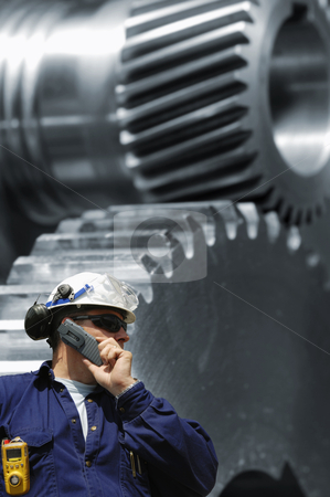 Engineering and technology stock photo, civil engineer in hard-hat with giant gears machinery in background, steel and metal works by lagereek