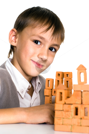 Handsome boy builds a toy castle  stock photo, handsome boy builds a toy castle on a white background by Alevtina Guzova
