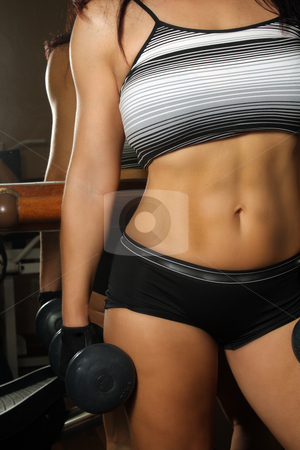 Athletic Female Torso, close-up, front view stock photo, A close-up shot of the torso of a female dressed in fitness wear, holding a hand weight,facing the camera. by Carl Stewart