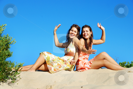 Two young woman having fun on the beach on a summer day stock photo, Two young woman having fun on the beach on a summer day by tish1