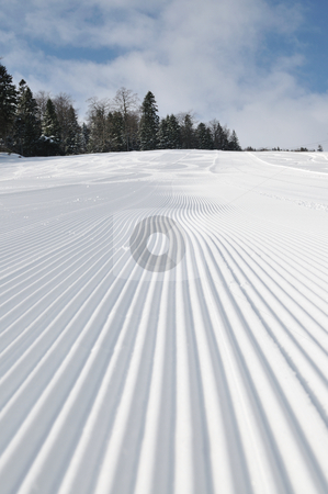 Tracks on ski slopes at beautiful sunny  winter day stock photo, tracks on ski slopes in snow at beautiful sunny  winter day with blue sky by Benis Arapovic