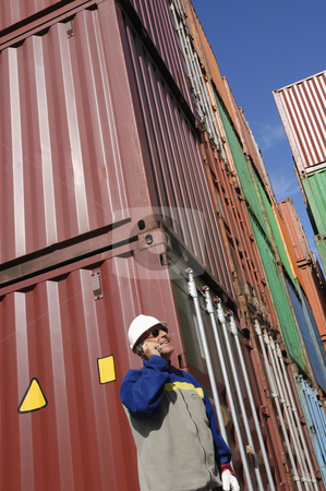 Port worker with containers stock photo, dock and port worker with stacks of containers in background by lagereek