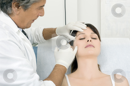 Young caucasian woman receiving an injection of botox from a doctor stock photo, young caucasian woman receiving an injection of botox from a doctor by ambrophoto
