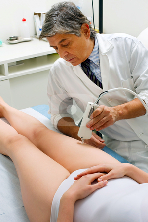 Caucasian woman receiving laser treatment at the leg from a male doctor stock photo, caucasian woman receiving laser treatment at the leg from a male doctor by ambrophoto