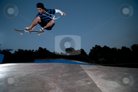 Skateboarder on a ollie stock photo, Skateboarder on a ollie at night at the local skatepark. by Homydesign