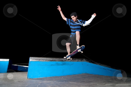 Skateboarder on a slide stock photo, Skateboarder on a slide at night at the local skatepark. by Homydesign