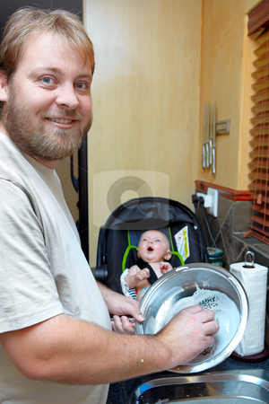 Son and father washing dishes. stock photo, young man washing the dishes with a smile while a baby boy keeps him company in a chair. by lubavnel