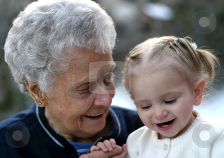 Laughing with Grandma stock photo, Sweet old woman shares a laugh with her great, great granddaughter by allihays