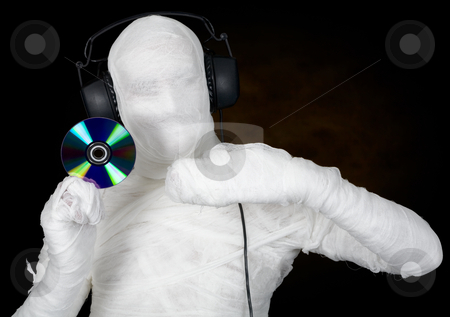 DJ costume mummy with ear-phones and disc stock photo, DJ in costume mummy with ear-phones and disc on black by Alexey Romanov