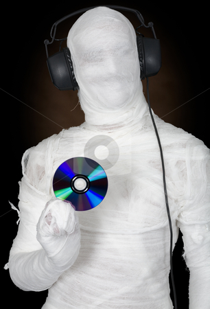 Man in bandage with ear-phones and disc stock photo, Man in bandage with ear-phones and disc on black by Alexey Romanov