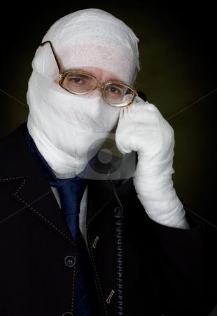 Man in bandage calling on phone stock photo, Man in bandage with eyeglasses  calling on phone by Alexey Romanov