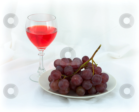 Still-life with a glass of red wine and grapes stock photo, Still-life with a glass of red wine and grapes on a white background by Alexey Romanov