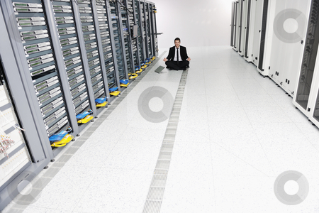 Business man practice yoga at network server room stock photo, young handsome business man in black suit practice yoga and relax at network server room while representing stress control concept by Benis Arapovic
