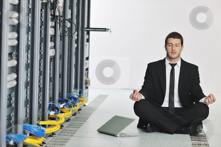 Business man practice yoga at network server room stock photo, young handsome business man in black suit and tie practice yoga and relax at network server room while representing stres control concept by Benis Arapovic