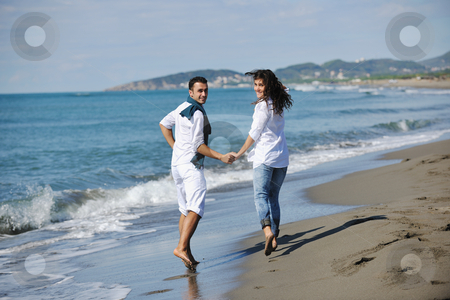 Happy young couple have fun at beautiful beach stock photo, happy young couple in white clothing  have romantic recreation and   fun at beautiful beach on  vacations by Benis Arapovic