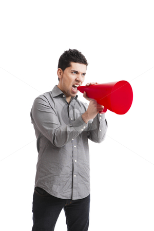 Shouting into a megaphone stock photo, Young man shouting into a megaphone over a white background  by ikostudio