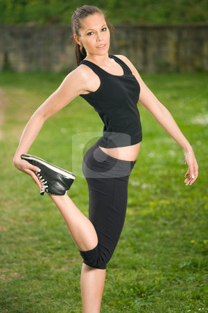 Just stretching... stock photo, Gorgeous young slender fitness girl stretching outdoors in nature. by exvivo