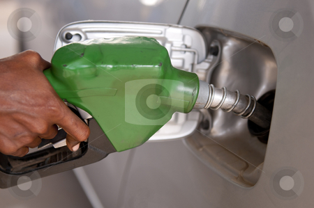 Fuel Prices stock photo, close-up of a mens hand refilling the car with a gas pump by Arvind Balaraman