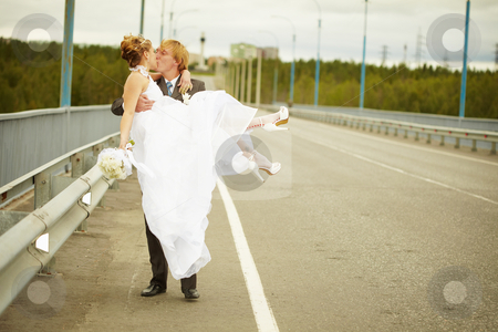 Groom carries his bride in his arms on bridge stock photo, The groom carries his bride in his arms on the bridge by Alexey Romanov