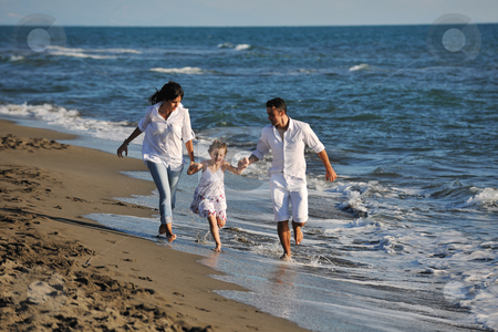 Happy young  family have fun on beach stock photo, happy young family in white clothing have fun at vacations on beautiful beach  by Benis Arapovic