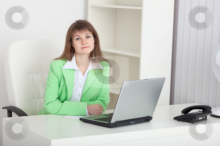 Beautiful young girl - manager sits at a table in office stock photo, The beautiful young girl - the manager sits at a table at office by Alexey Romanov