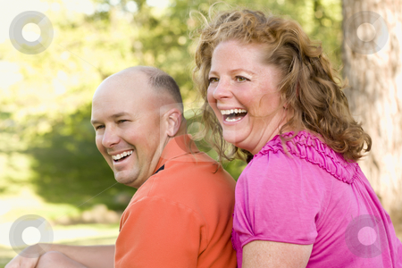 Happy Attractive Couple Laughing in Park stock photo, Happy Attractive Couple Laughing in the Park. by Andy Dean