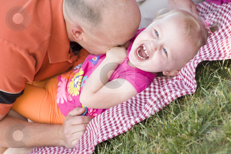Loving Dad Tickles Daughter in Park stock photo, Loving Dad Tickles His Daughter in the Park. by Andy Dean