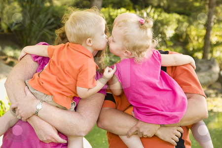 Mom and Dad Holding Kissing Brother and Sister Toddlers stock photo, Mom and Dad Holding Kissing Brother and Sister Toddlers in the Park. by Andy Dean