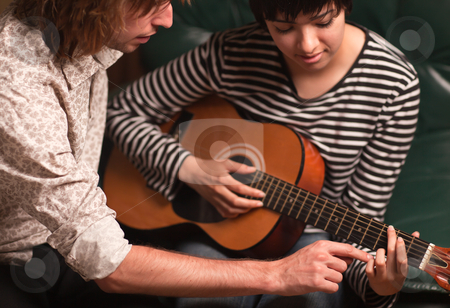 Young Musician Teaches Female Student To Play the Guitar stock photo, Young Male Musician Teaches Female Student How To Play the Guitar. by Andy Dean