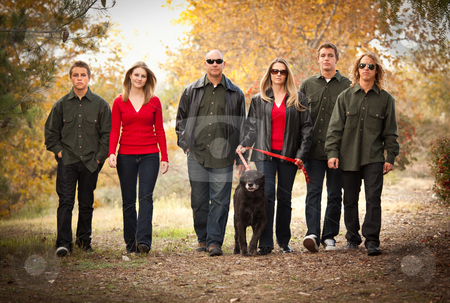 Attractive Family Portrait Walking Outdoors stock photo, Attractive Family Portrait Walking Outdoors with Their Dog. by Andy Dean